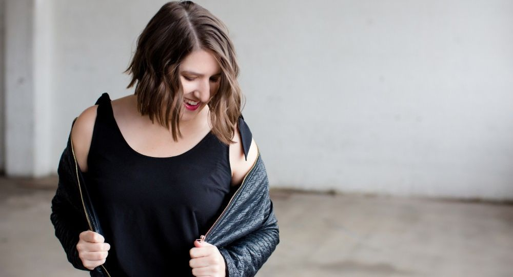 Photo of brunette woman dressed in all black looking down