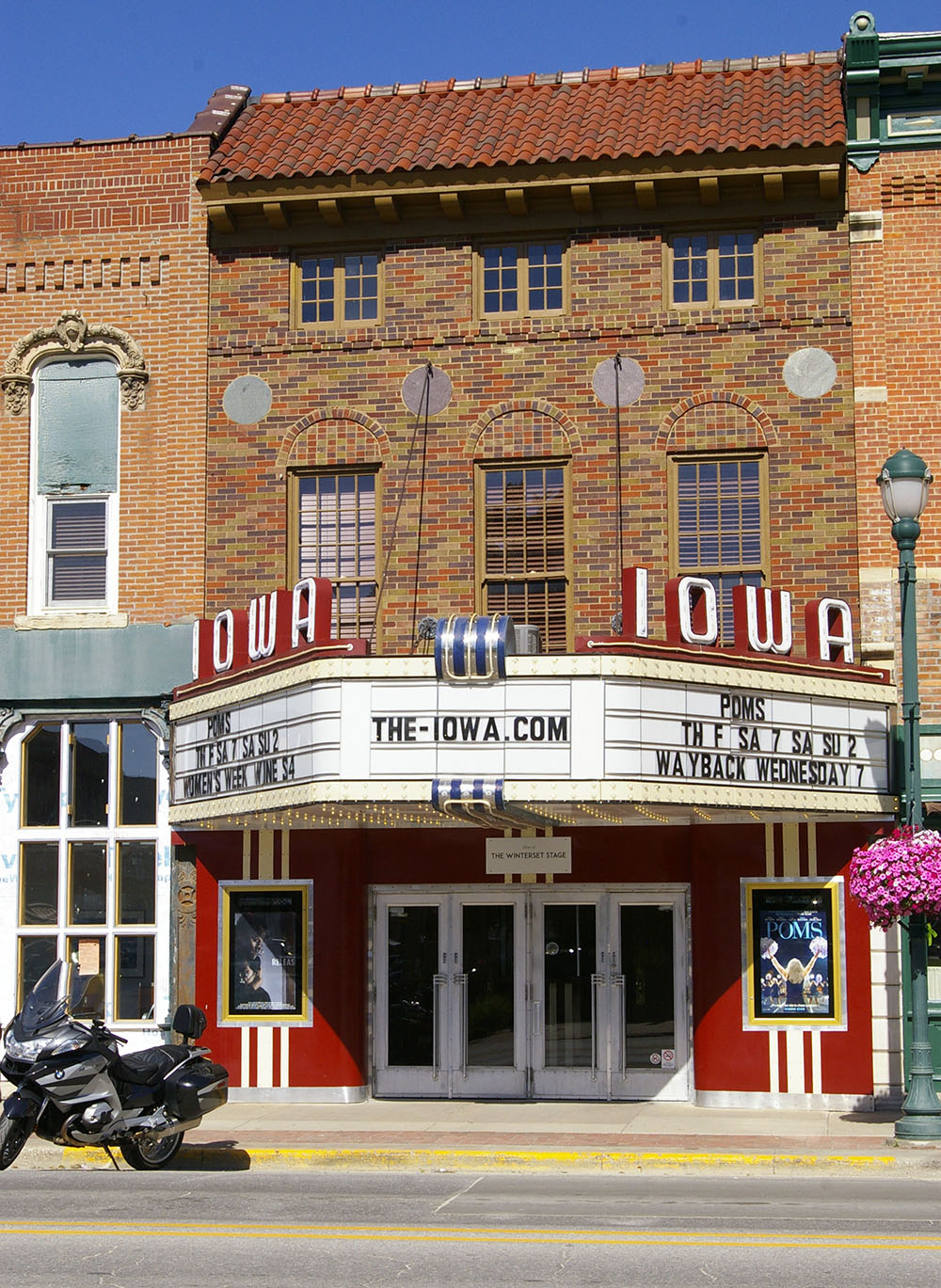 Brick exterior and white and red marquee of the Iowa Theater in Winterset, Iowa