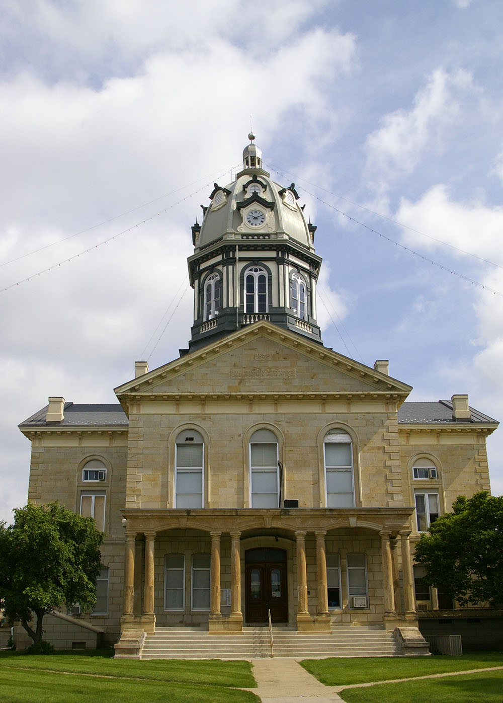 Limestone building exterior with white and navy bell tower of the Madison County Courthouse in Winterset, Iowa