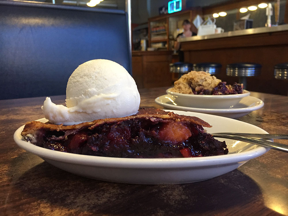 Blackberry peach pie a la mode with blueberry crisp in the background on a table at Northside Cafe in Winterset, Iowa