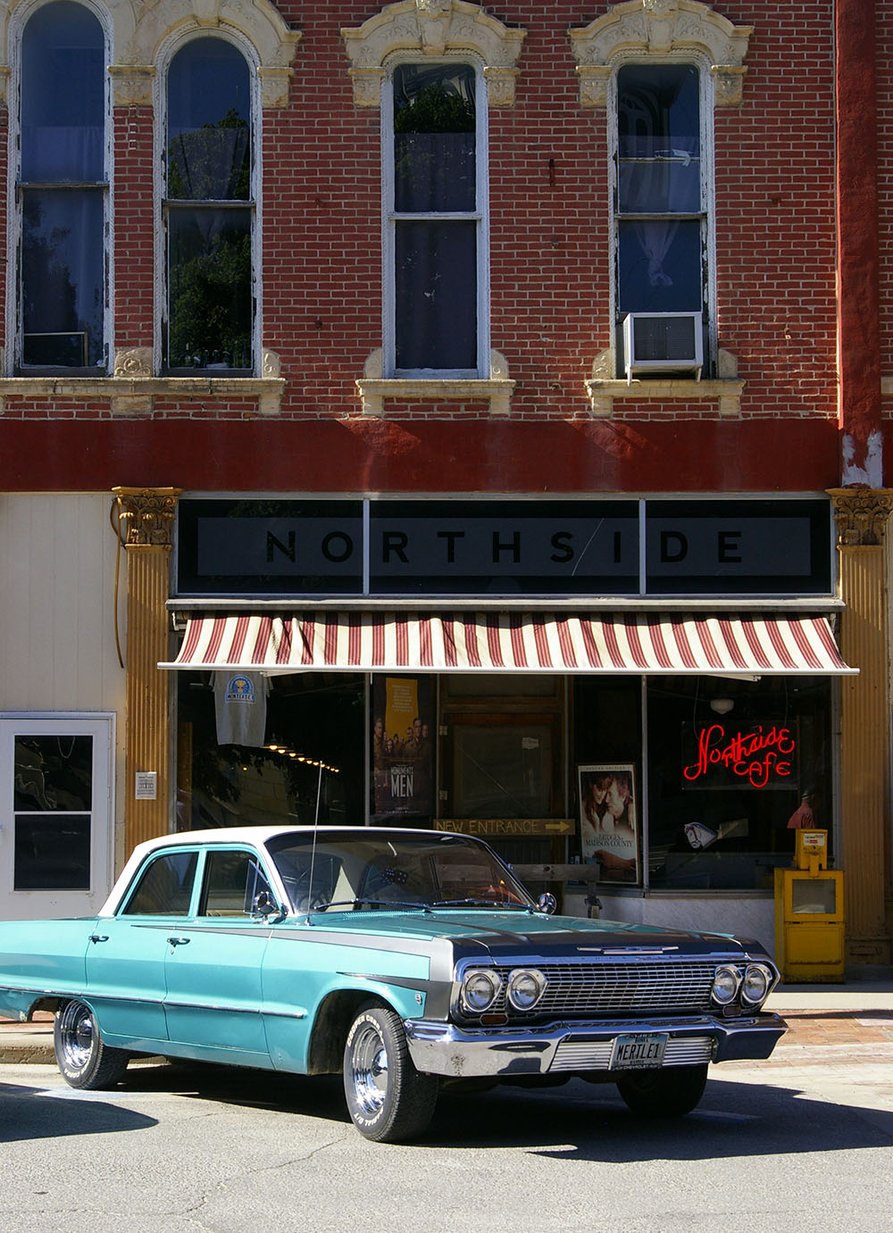Brick facade and striped awning of the iconic Northside Cafe with a classic teal car in front in Winterset, Iowa