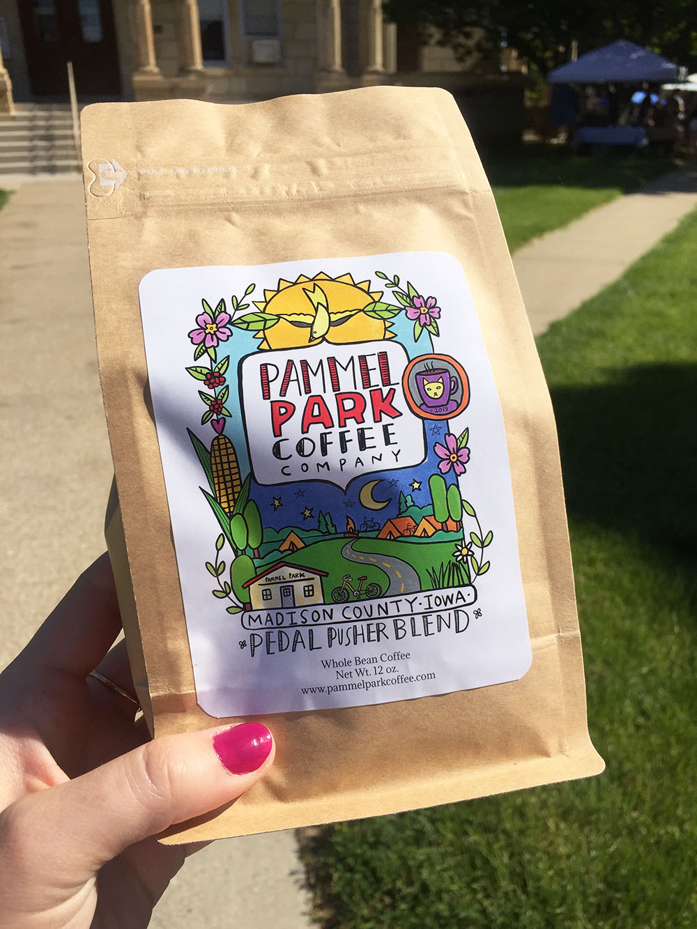 Bag of coffee beans from Pammel Park Coffee with colorful illustrated label at the Winterset Farmers' Market in Winterset, Iowa