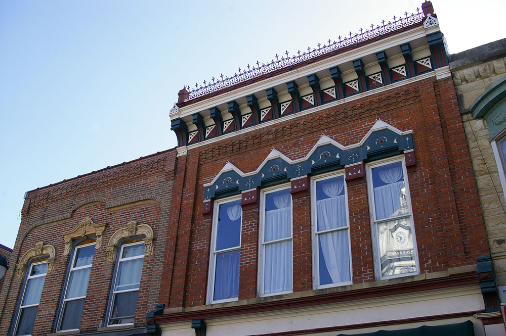 Brick facade and colorful window decoration of a shop on the square in Winterset, Iowa