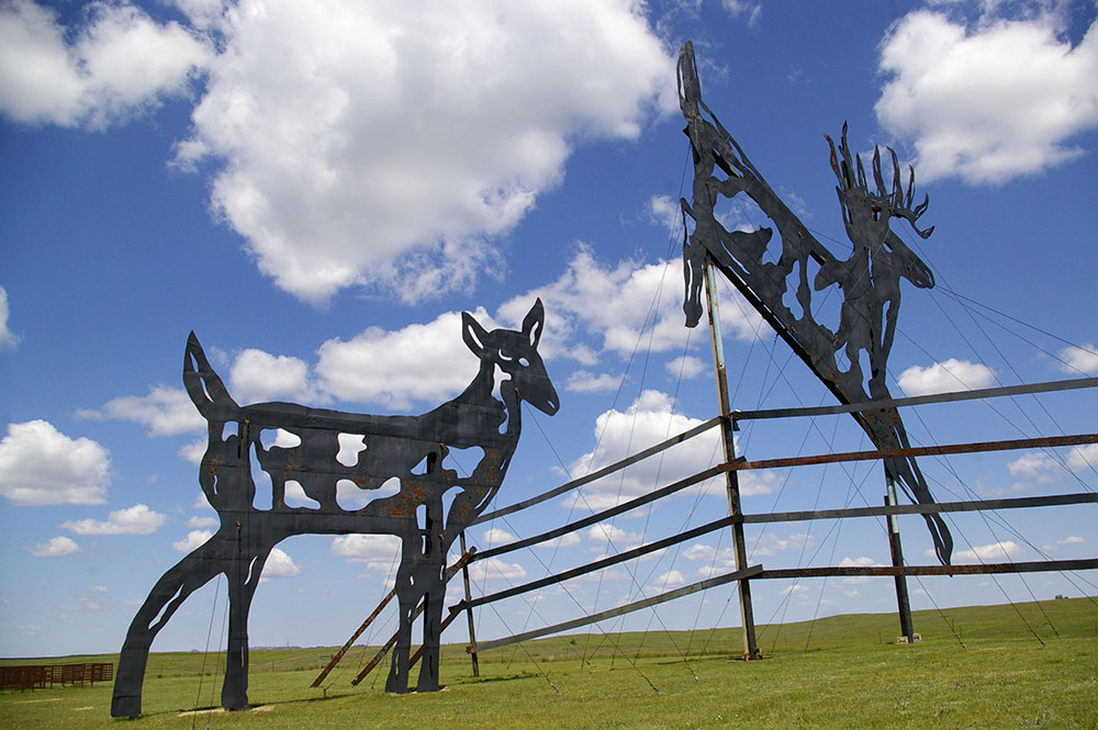 Large black metal sculpture featuring a male and female deer jumping a fence along the Enchanted Highway near Regent, North Dakota