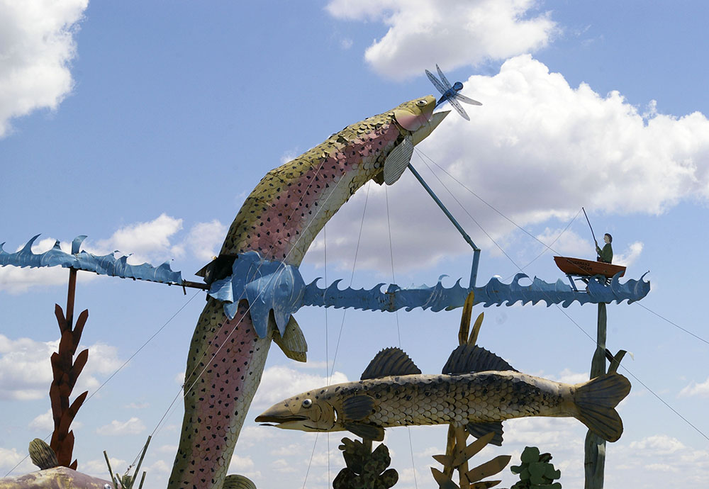 Metal fish jumping in the air to catch a dragonfly with a small fisherman in a boat in the background along the Enchanted Highway near Regent, North Dakota