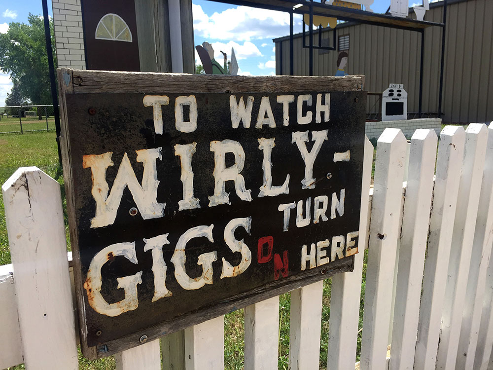 Sign in front of mechanical wirly gigs at the Enchanted Highway Gift Shop in Regent, North Dakota