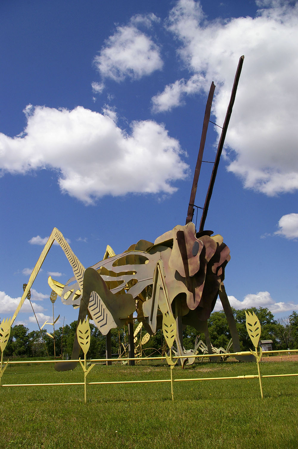 Large yellow, brown and green grasshopper made out of metal behind yellow metal fence shaped like cornstalks