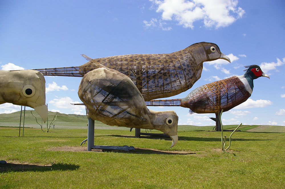 Large metal pheasant sculpture with red and green head along the Enchanted Highway near Regent, North Dakota