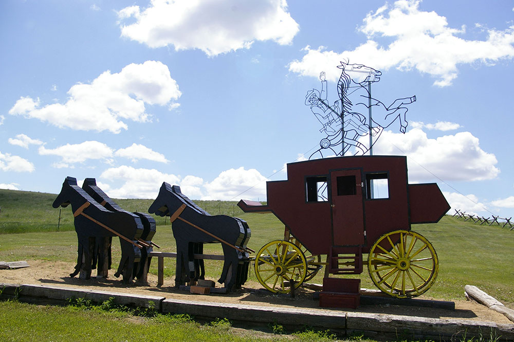 Large metal outline of Teddy Roosevelt riding a horse in back of wooden horses and stagecoach along the Enchanted Highway near Regent, North Dakota