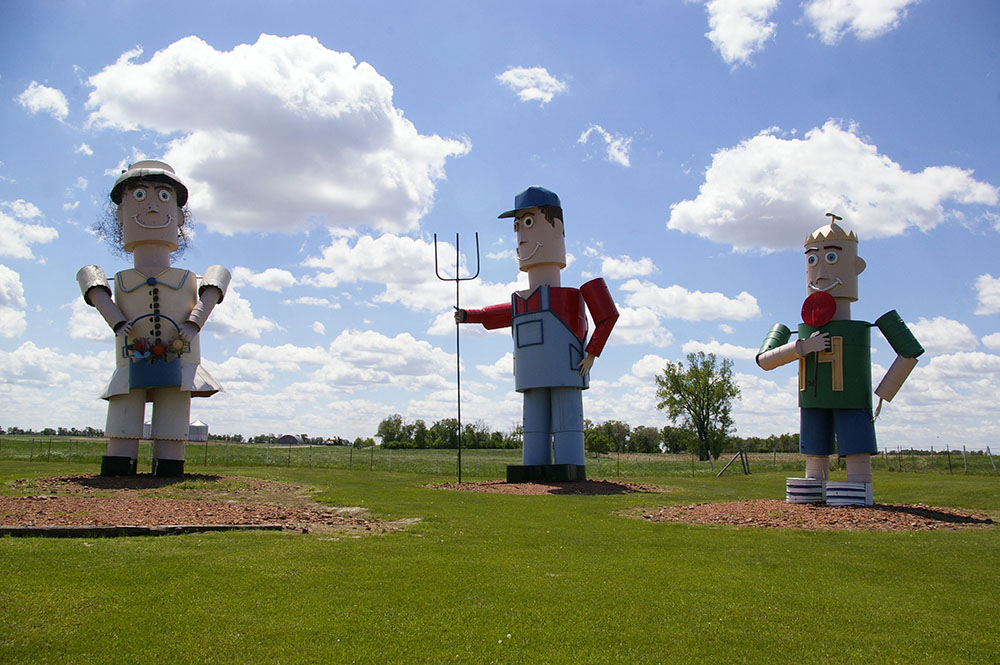 Three large metal sculptures that look like a woman, man and child along the Enchanted Highway near Regent, North Dakota
