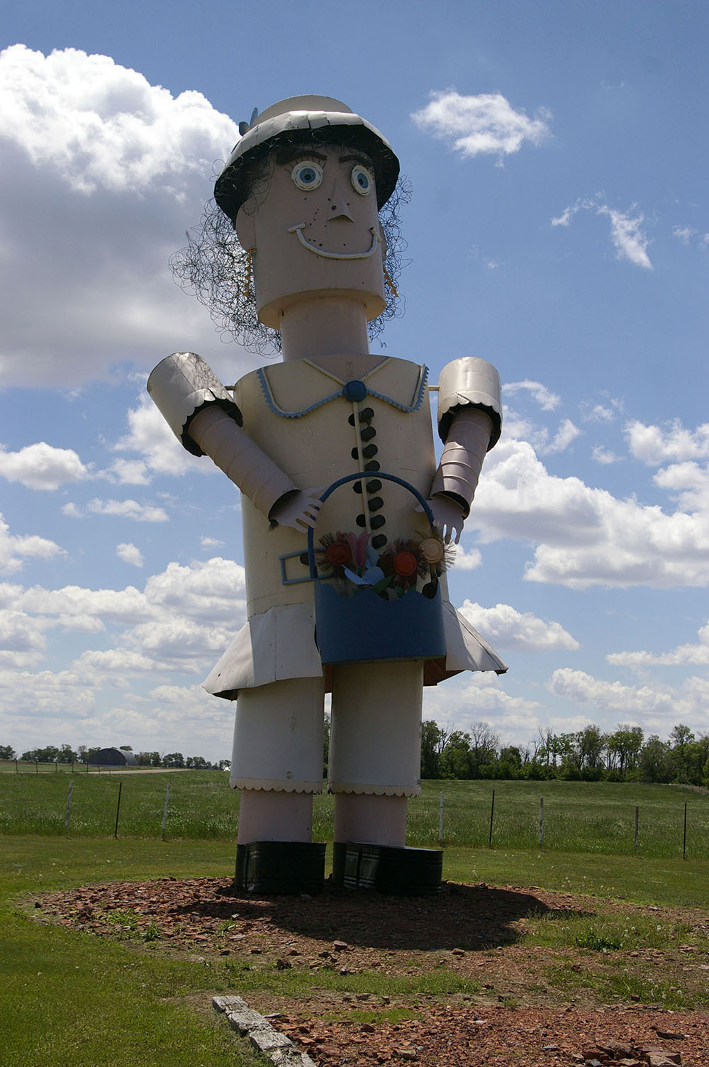 Large metal sculpture of woman holding a bucket of flowers along the Enchanted Highway near Regent, North Dakota