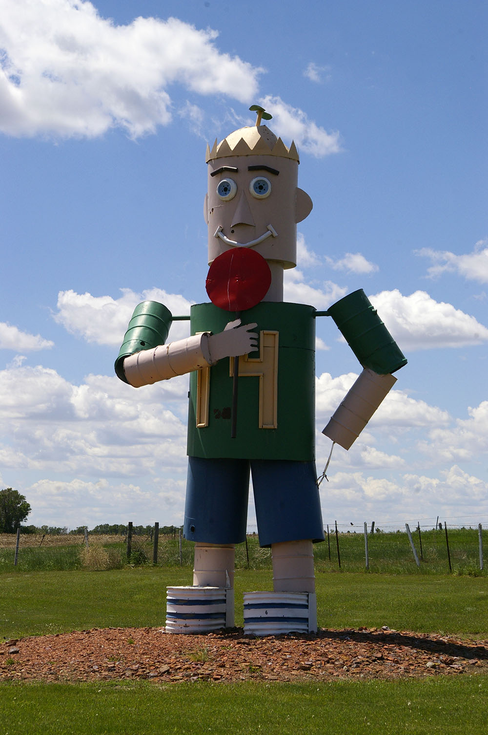 Large metal sculpture of a boy with a propellor hat licking a lollipop along the Enchanted Highway near Regent, North Dakota