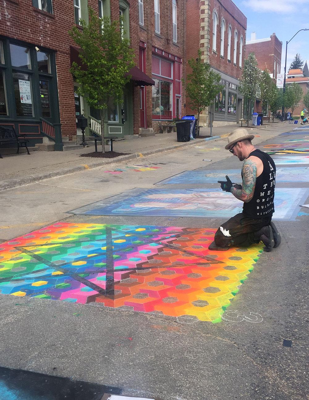 Artist creating rainbow chalk art during Mount Vernon's 2019 Chalk the Walk