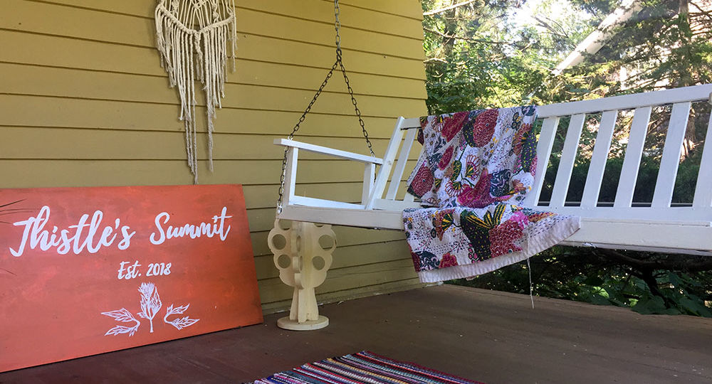 "White front porch swing with colorful blanket and orange sign reading ""Thistle's Summit"" at Thistle's Summit in Mount Vernon, Iowa"