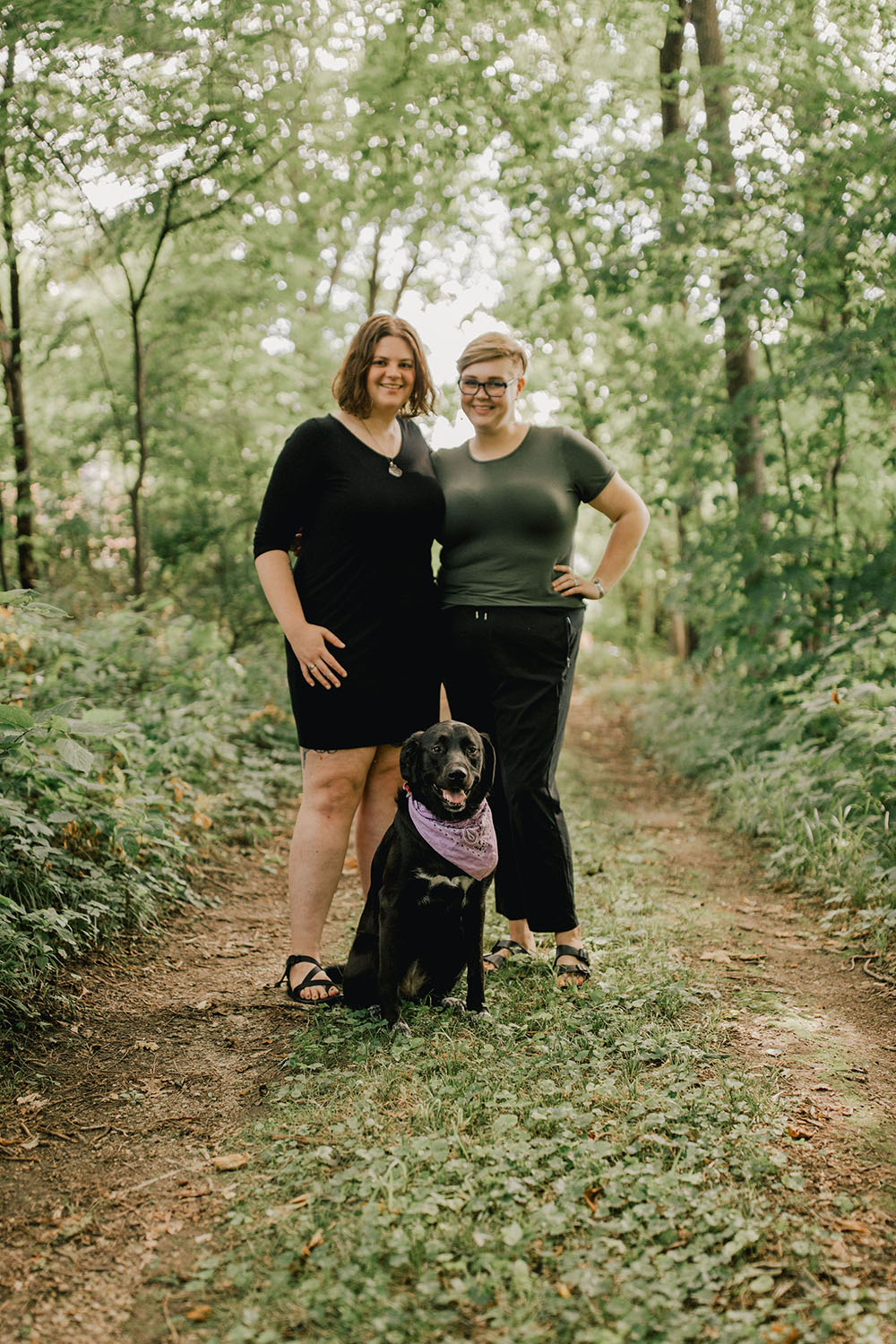 Two people standing with a black dog in a wooded lane near Mount Vernon, Iowa
