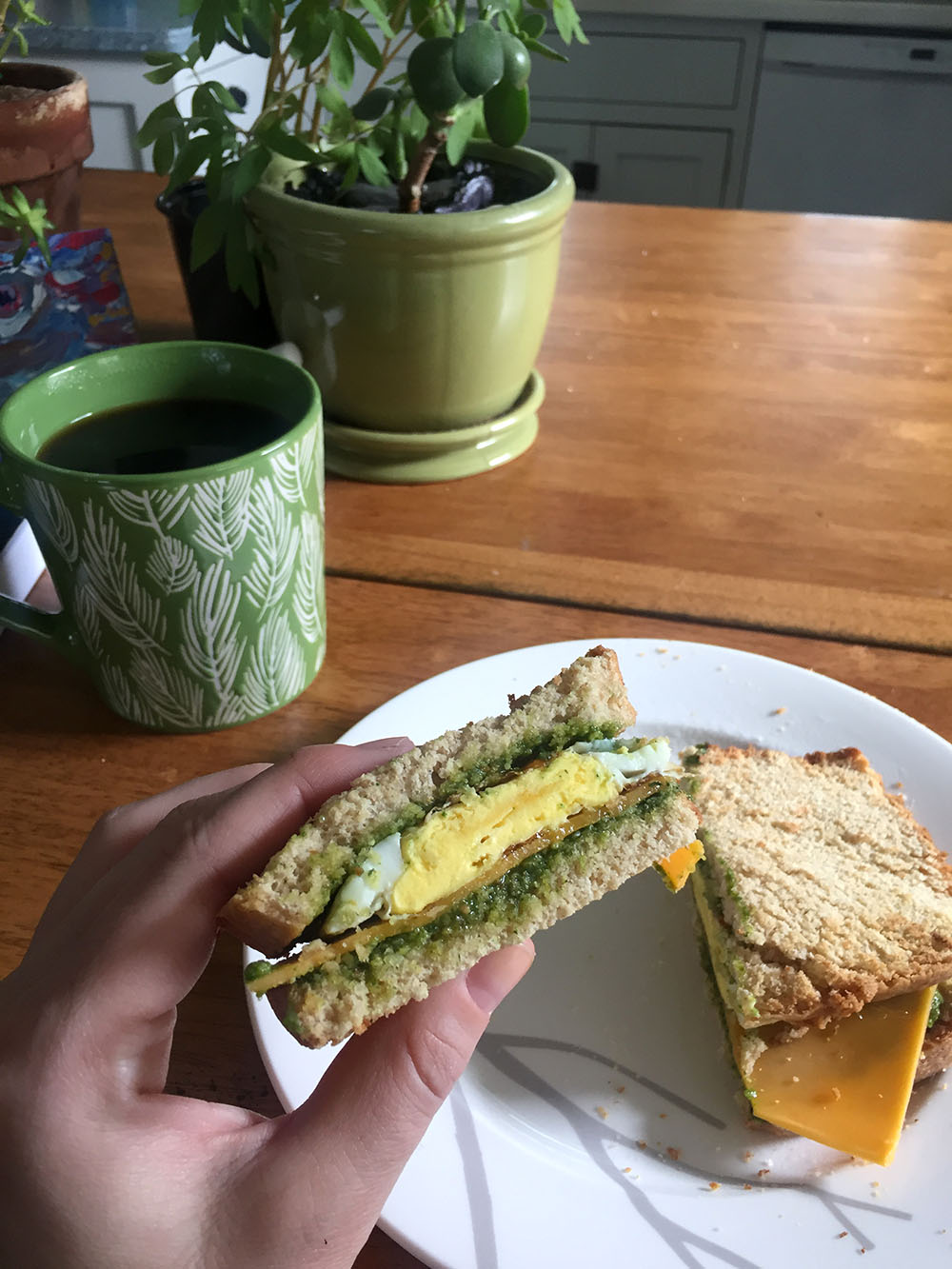 Coffee mug beside breakfast sandwich with pesto, egg and cheese at Thistle's Summit in Mount Vernon, Iowa