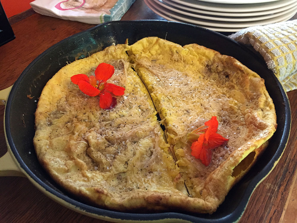 Dutch baby in a cast iron skillet with orange flowers at Thistle's Summit in Mount Vernon, Iowa