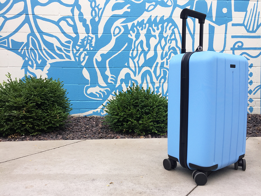 Blue Chester Minima Carry-On Spinner Suitcase in front of blue and white mural