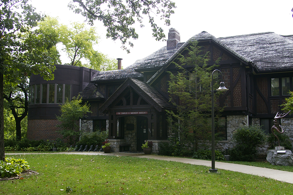 Exterior of brown lodge style building with slopping roof that serves as the Charles H. MacNider Art Museum in Mason City, Iowa