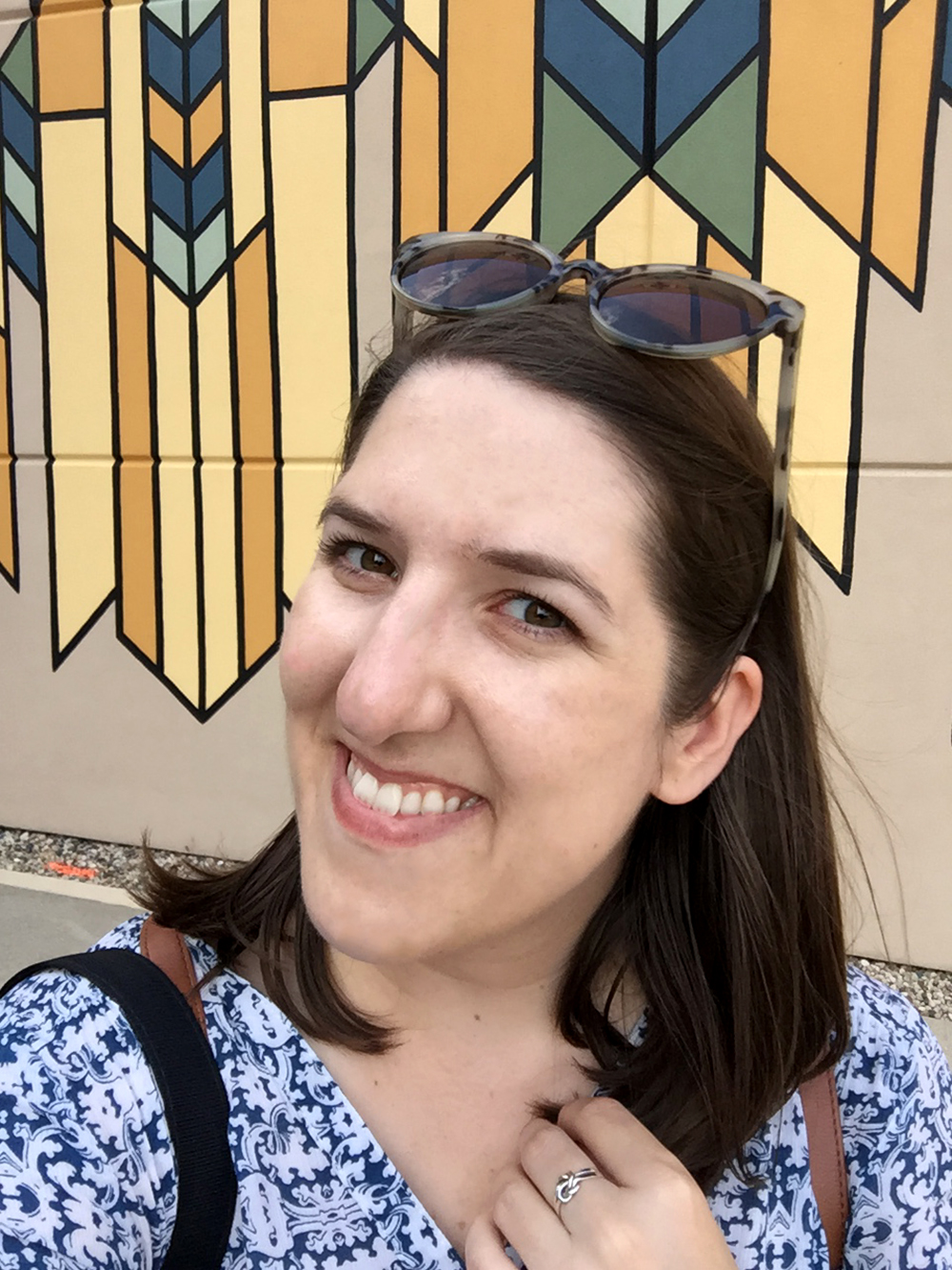 Selfie of brunette woman in front of Frank Lloyd Wright-inspired public art in Mason City, Iowa