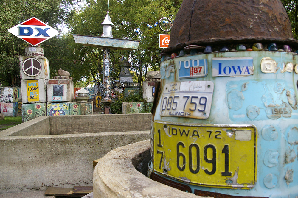 License plate covered pole in front of folk art at the Rancho Deluxe in Mason City, Iowa