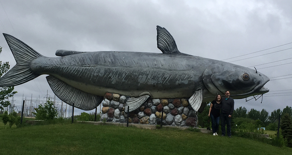 Two people standing in front of a giant gray catfish statue named the Wahpeton Wahpper, the world's largest catfish, near Wahpeton, North Dakota