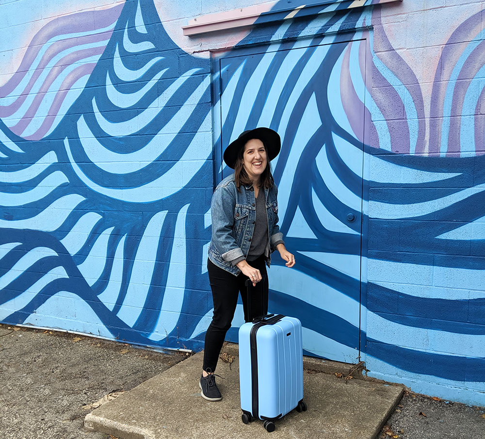 Brunette woman in a jean jacket and hat with a blue Chester Minima Carry-On Spinner Suitcase in front of a blue and purple mural of waves