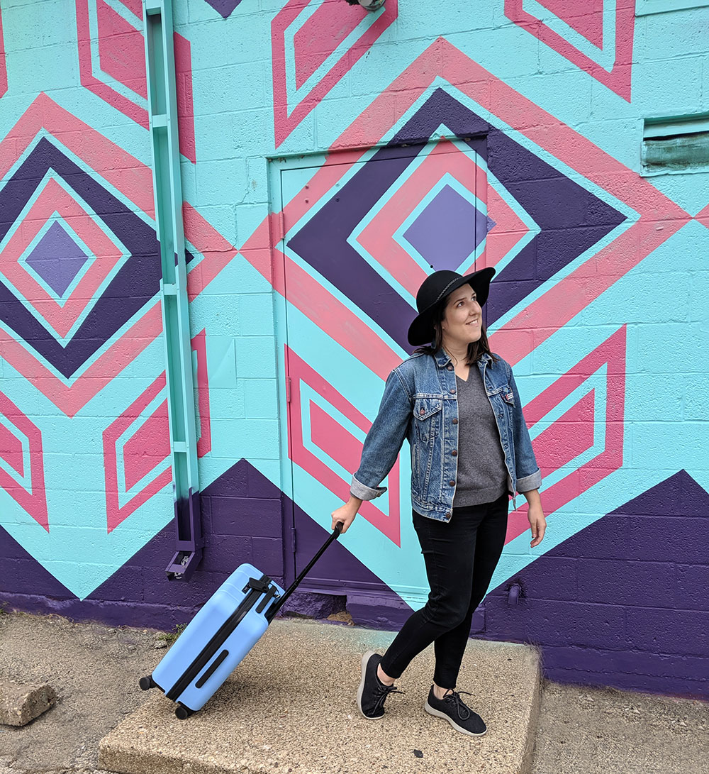 Brunette woman in a jean jacket and hat with a blue Chester Minima Carry-On Spinner Suitcase in front of a teal and pink mural