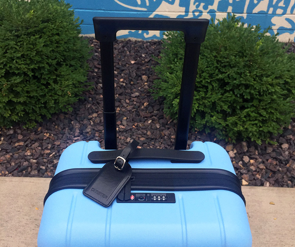 Top of a blue Chester Minima Carry-On Spinner Suitcase in front of blue and white mural