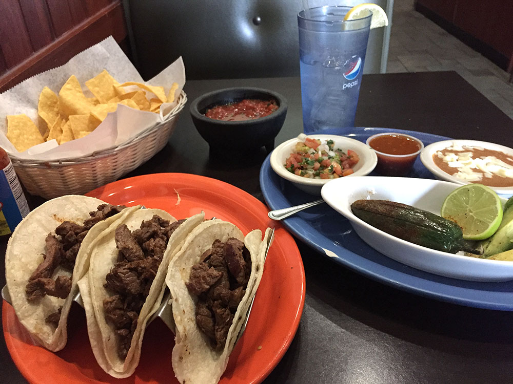 Three steak tacos with basket of tortilla chips and toppings at Las Palmas Mexican Restaurant in Mason City, Iowa