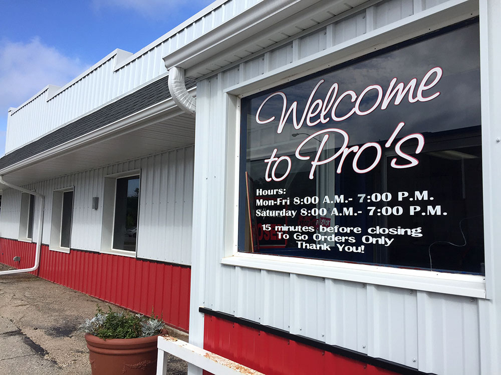 "Exterior of white and red building with a window reading ""Welcome to Pro's"" at Pro's Sandwich Shop in Mason City, Iowa"
