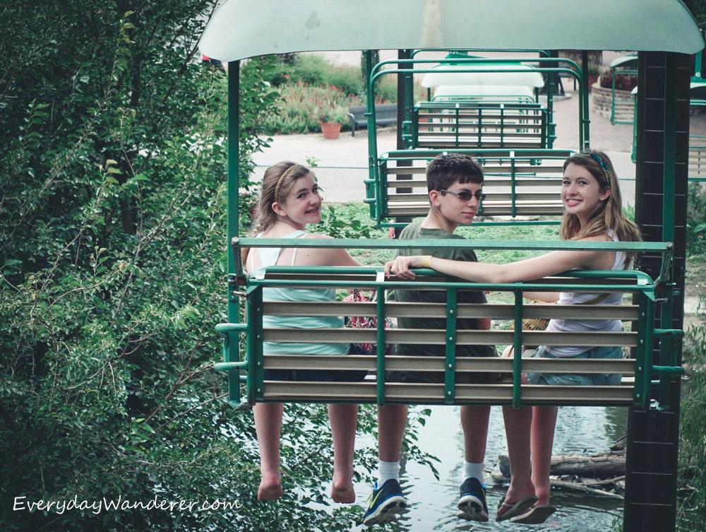 Three children riding on a green chair lift