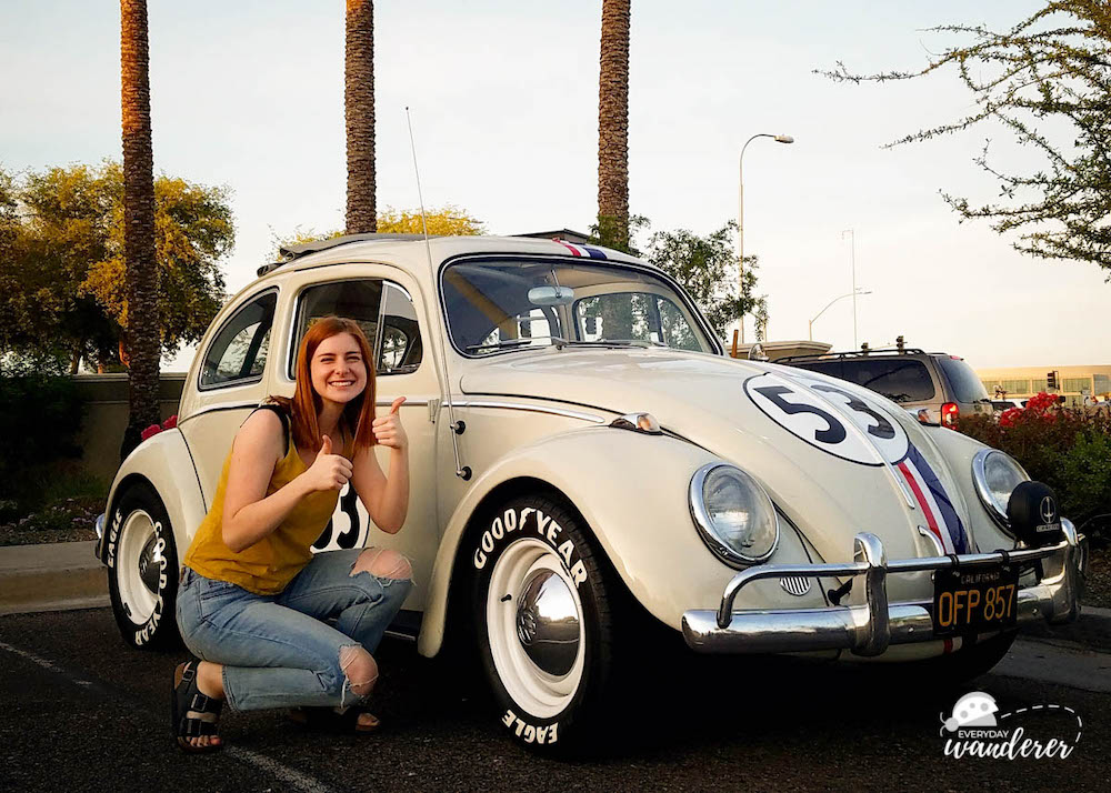 Girl with red hair next to a tan Volkswagen Beetle painted like Herbie the Love Bug