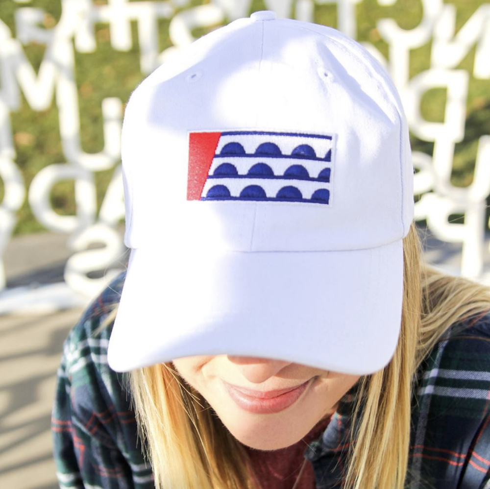 Blonde woman wearing white baseball hat with the Des Moines flag embroidered on it