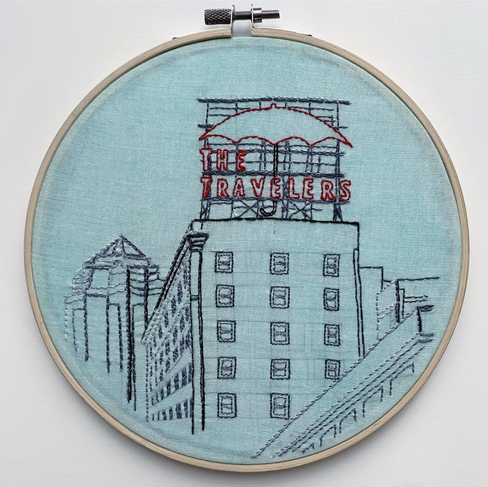Embroidery hoop with design of the Travelers' sign in downtown Des Moines