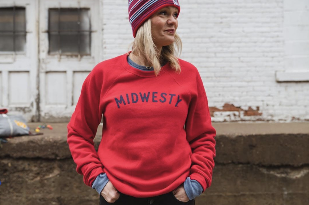 Blonde woman wearing red crewneck sweatshirt that says Midwesty