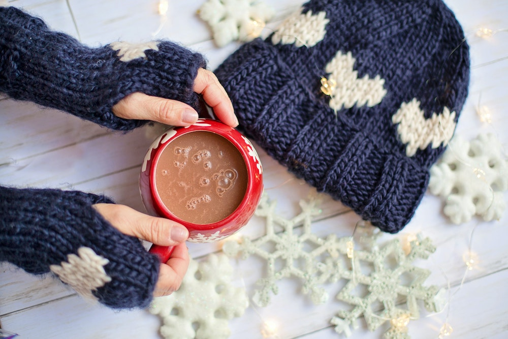 Hands wearing navy gloves holding a red mug of hot cocoa against a white snowflake background | Olio in Iowa's 2020 Holiday Gift Guide