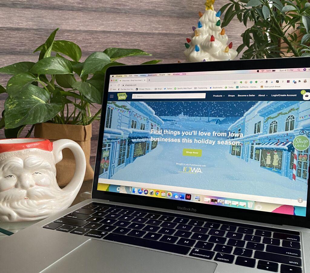 Computer screen with Shop Iowa site on screen next to a mug shaped like Santa's face