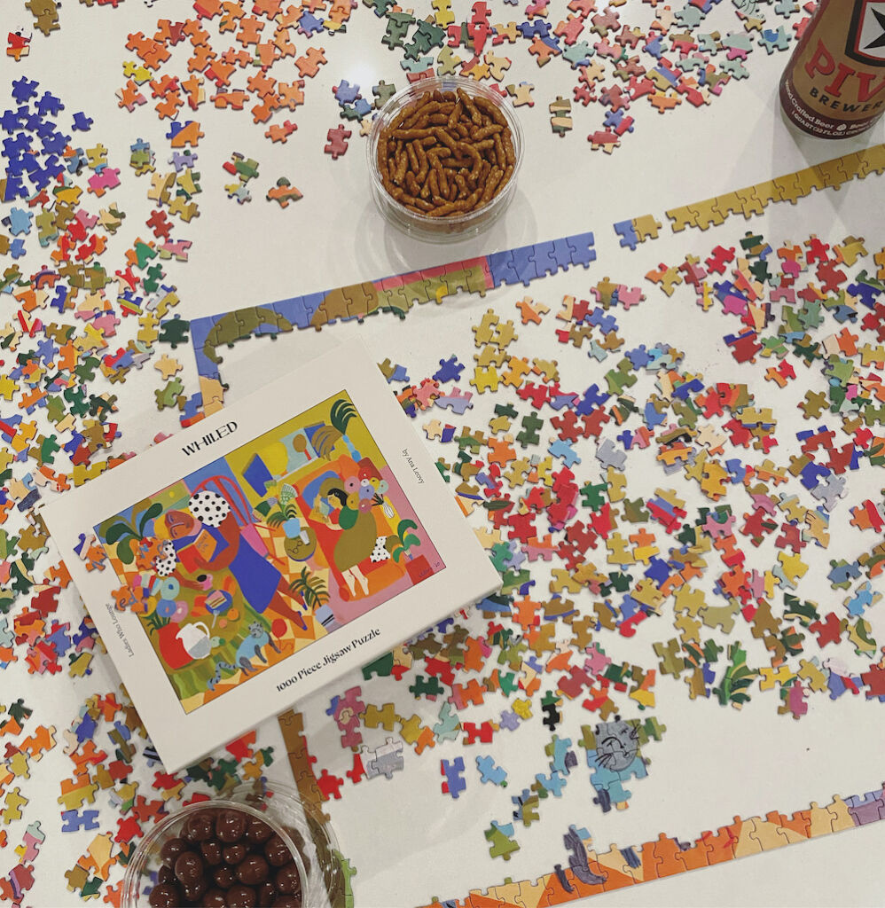 Whiled Ladies Who Lounge puzzle in-progress surrounded by snacks