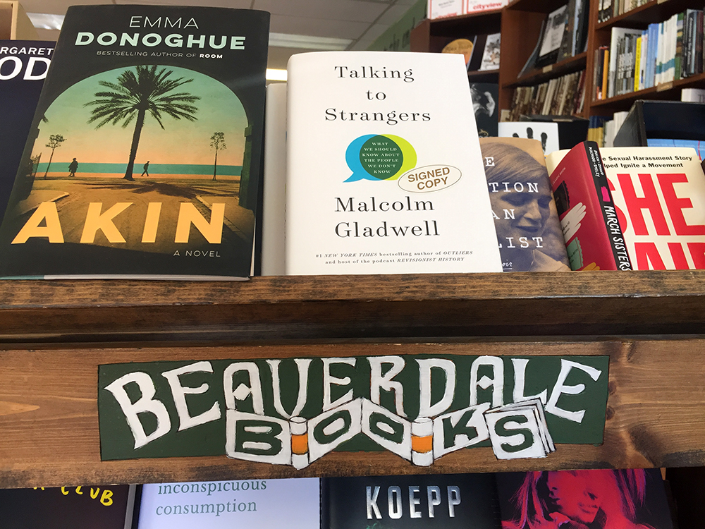 Stack of books on a shelf that says Beaverdale Books at Beaverdale Books in Des Moines, Iowa