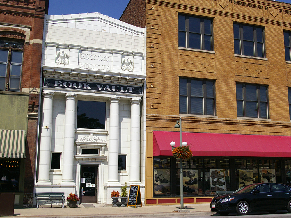 White marble exterior of a historic bank now home to the Book Vault in Oskaloosa, Iowa