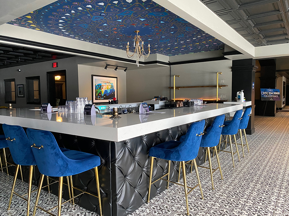 Bar with painted mural ceiling and blue velvet chairs at The Highlander Hotel in Iowa City, Iowa