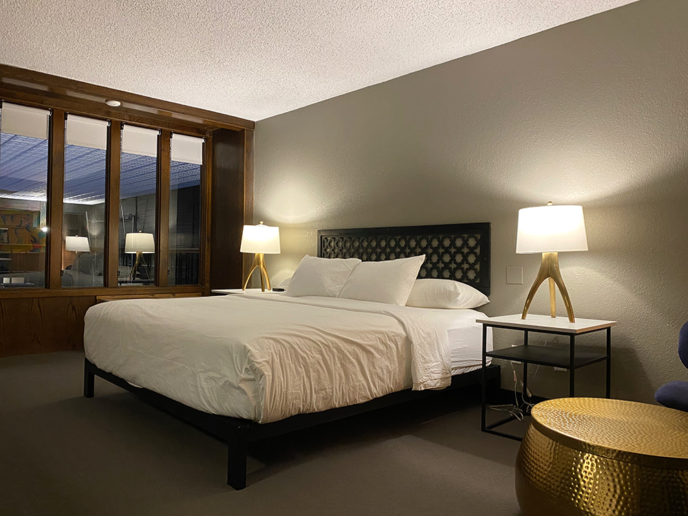 Bed with white linens and gold accent table and lamps at The Highlander Hotel in Iowa City, Iowa