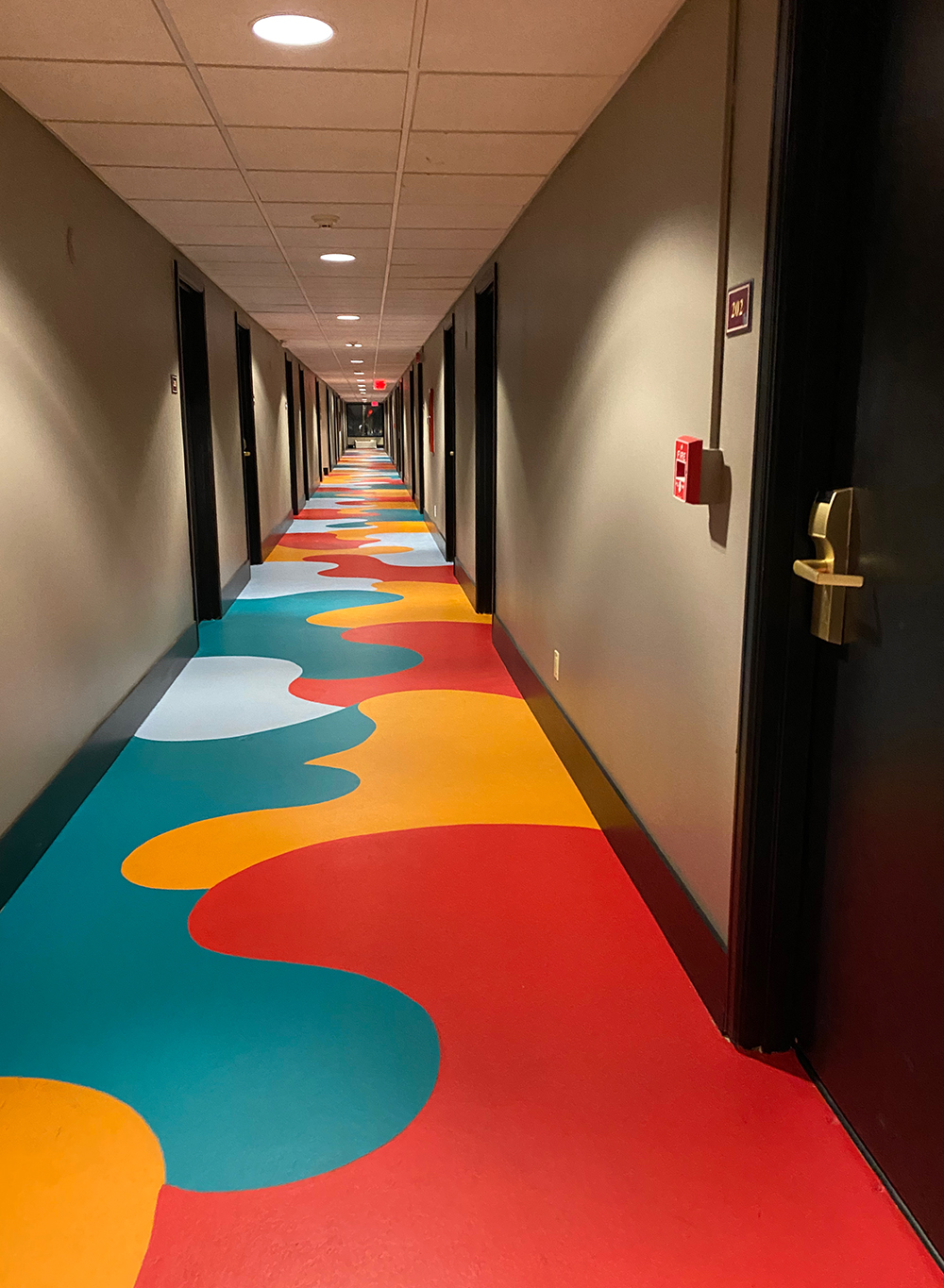 Hallway with red, orange and teal blobs painted on the floor
