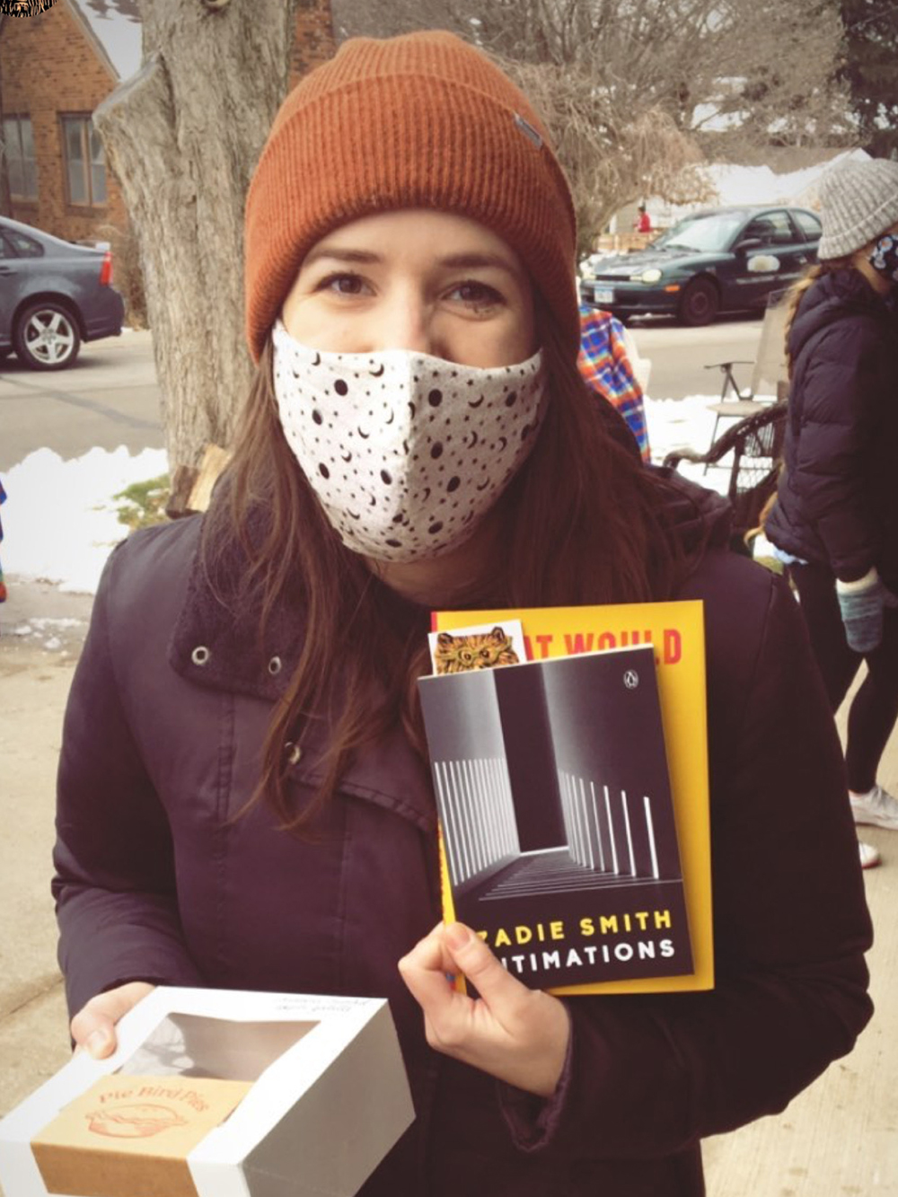 Woman wearing mask holding box of pies and two books at Storyhouse Bookpub holiday popup in Des Moines, Iowa