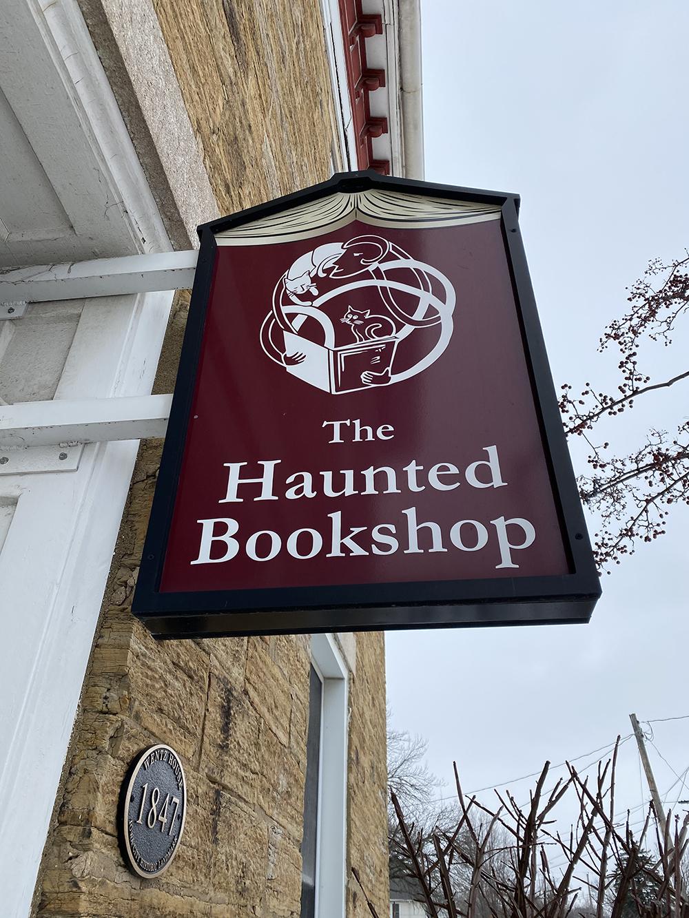 Maroon sign for The Haunted Bookshop in Iowa City, Iowa