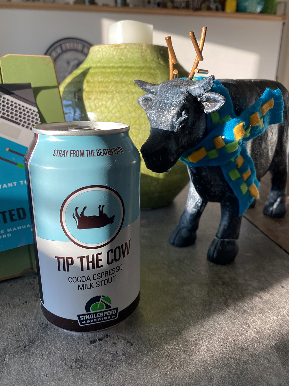 Can of Tip the Cow from Single Speed Brewing next to cow statue at New Day Dairy Guest Barn in Clarksville, Iowa