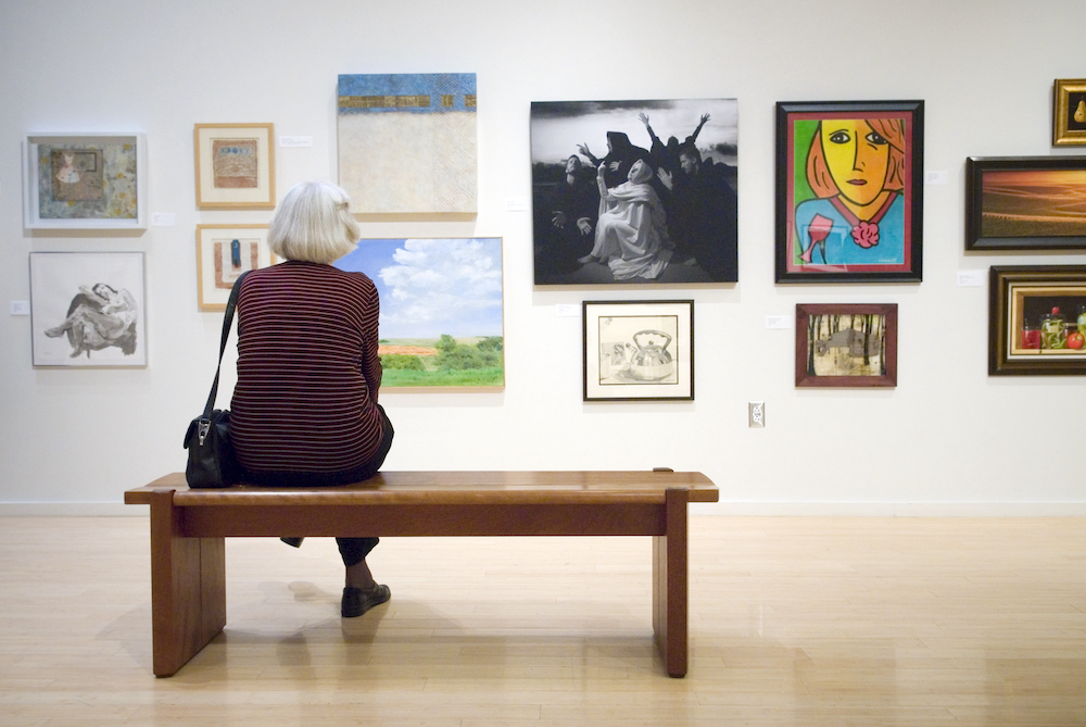 Person sitting on a bench looking at art
