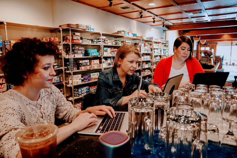 Three women sitting at a bar using laptops with board games in the background