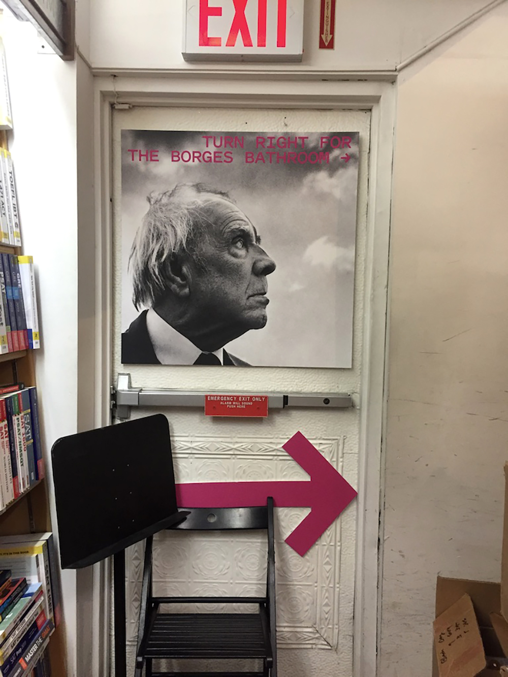 """Pink directional arrow and sign that says """"Turn right for the Borges Bathroom"""""""